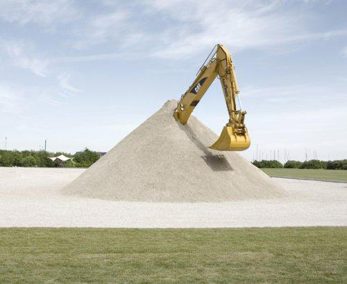 A backhoe operator covers his own machine in sand to show that DIY is not always the best option
